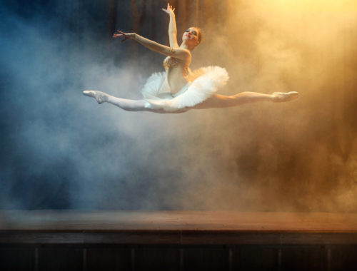 Ballet dancer performing on stage in theatre. There is a fog on the stage.